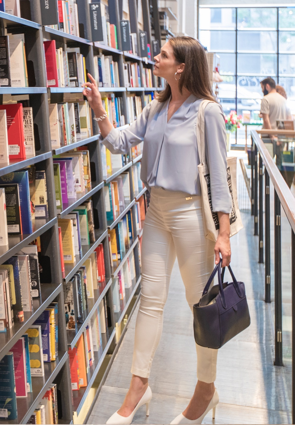 A brunette woman browses shelves at a NYC bookstore