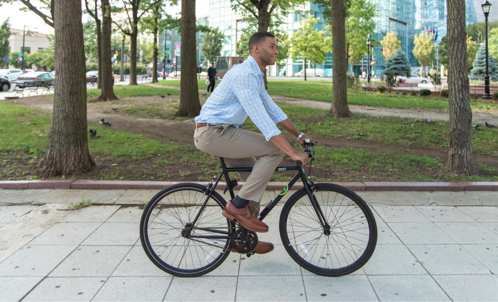 An African-American man in business attire rides a bike through an NYC neighborhood